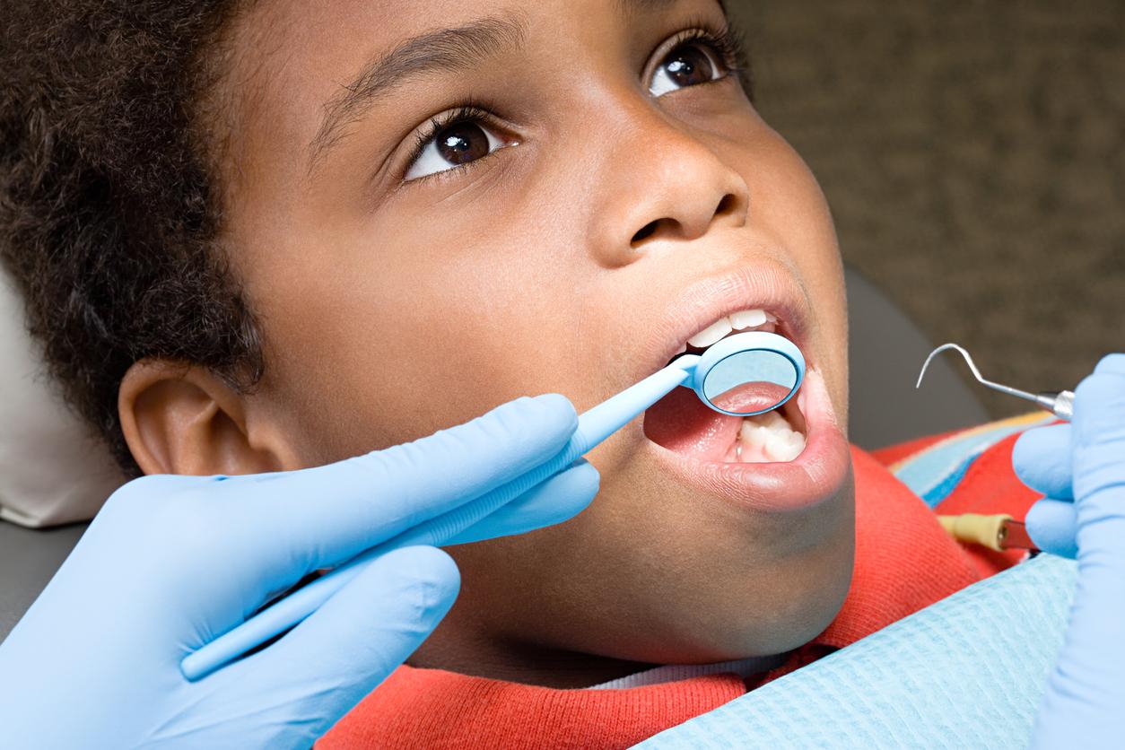 Boy having teeth examined