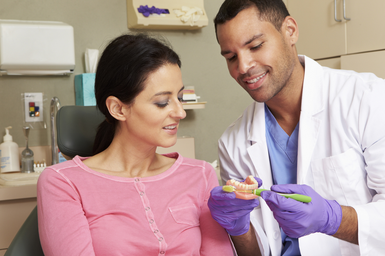 Dentist using props to show a patient how to brush her teeth